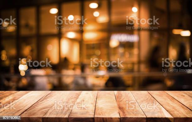 Wood table top on blurred of cafe with light gold in dark nigh or picture id929760662?b=1&k=6&m=929760662&s=612x612&h=bebaefpqkyzklqgzaumhdejavevjxzxhnma9of5xf6e=