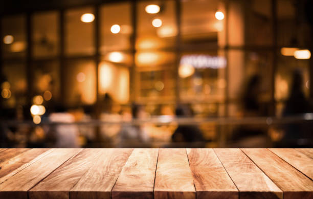 wood table top on blurred of cafe ( restaurant ) with light gold in dark nigh background.for montage product display or key visual layout. - bar zdjęcia i obrazy z banku zdjęć