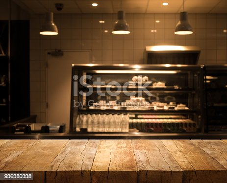 864907996istockphoto Wood table top on blurred of counter cafe shop with light bulb background 936380338