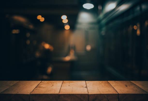holz tischplatte auf unscharf zähler café shop mit glühbirne. hintergrund für montage produktdarstellung oder key-visual-design - cafe stock-fotos und bilder