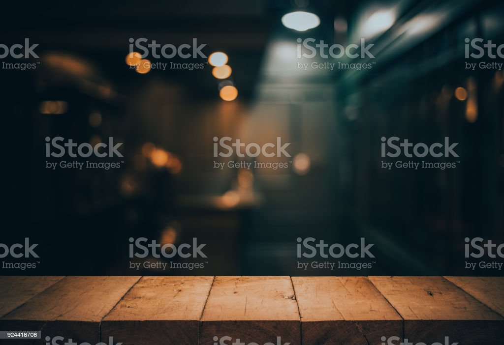 Wood table top on blurred of counter cafe shop with light bulb.Background for montage product display or design key visual стоковое фото