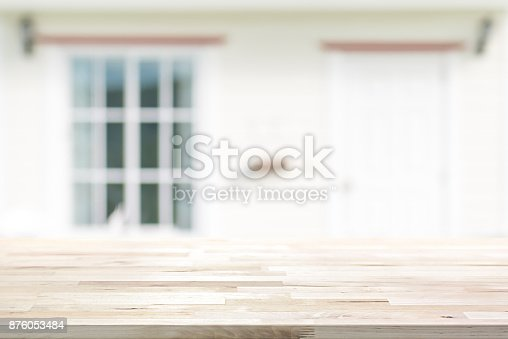 834157738istockphoto Wood table top on blurred white house front with door and glass window 876053484