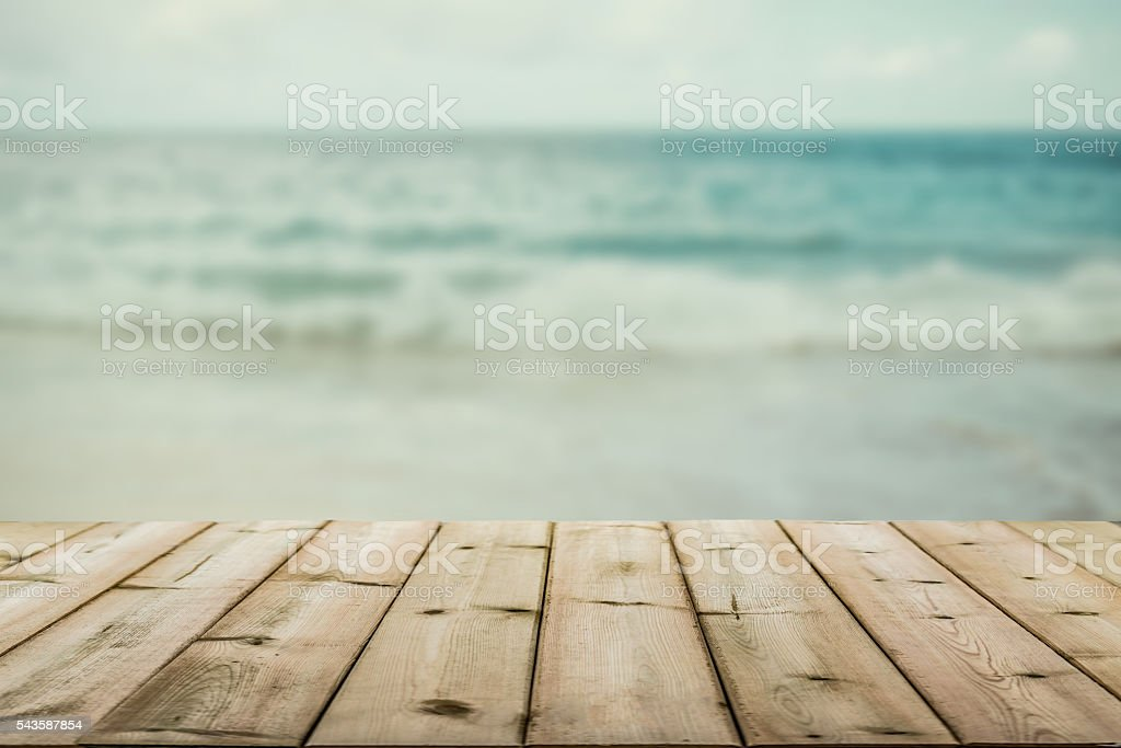 wood table top on blurry blue beach background stock photo