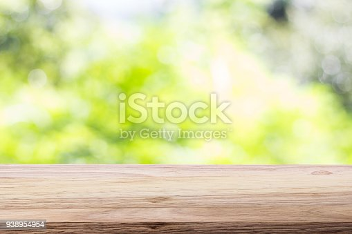 989111446istockphoto Wood table top on bokeh green bright background. For montage product display or design key visual layout 938954954