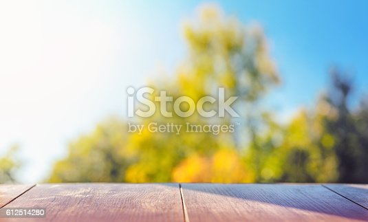 989111446istockphoto Wood table top on colorful blurred abstract outdoor background 612514280
