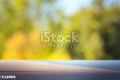 989111446istockphoto Wood table top on colorful blurred abstract outdoor background. 612515608