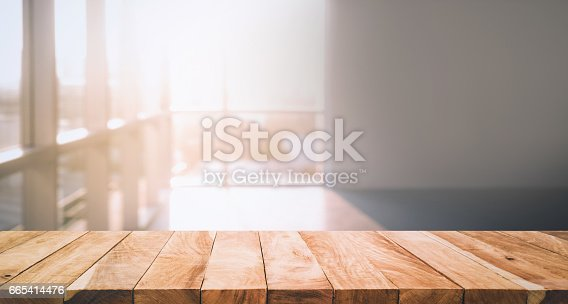 istock Wood table top on glass wall abstract background. 665414476