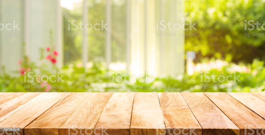 Wood table top on green from garden in morning background.