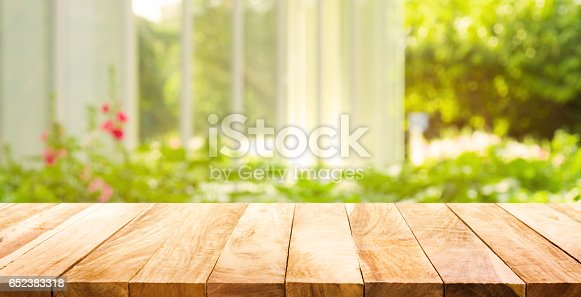 istock Wood table top on green from garden in morning background. 652383318