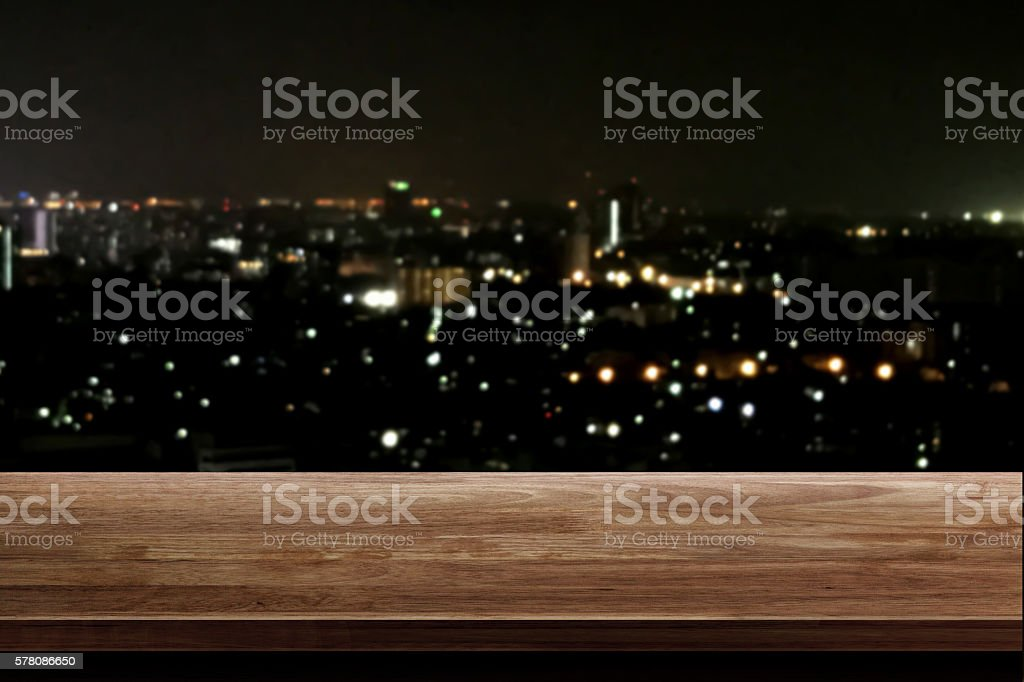 wood table top on night city background stock photo