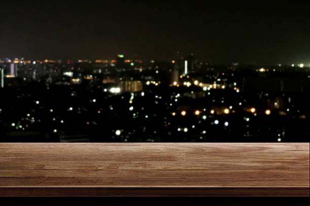 wood table top on night city background - regal schwarz stock-fotos und bilder