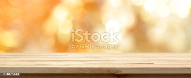istock Wood table top on shiny gold bokeh abstract background 624028444
