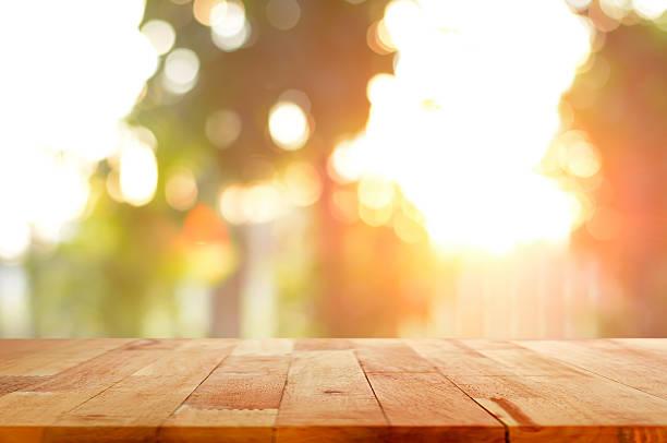 holz tisch mit glänzend bokeh hintergrund mit sonnenlicht - goldene bar stock-fotos und bilder