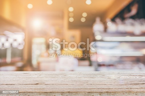 886308526istockphoto Wood table top with Abstract blur Coffee shop background 855256854