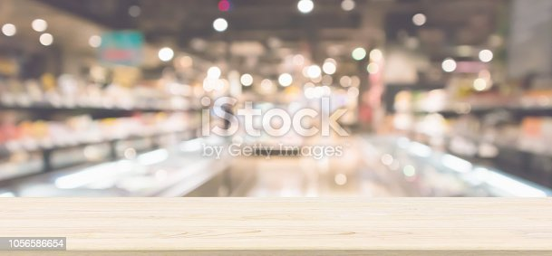 istock Wood table top with Abstract supermarket grocery store refrigerator blurred defocused background with bokeh light 1056586654