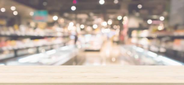 trä bordsskiva med abstrakt stormarknad livsmedelsbutik kylskåp suddig oskärpa bakgrunden med bokeh ljus - dagligvaruhandel, hylla, bakgrund, blurred bildbanksfoton och bilder