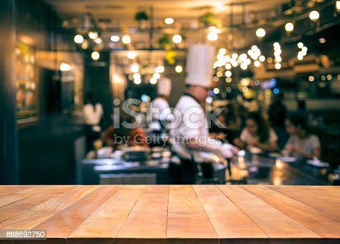 istock Wood table top with blur chef cooking in bar restaurant 888592750