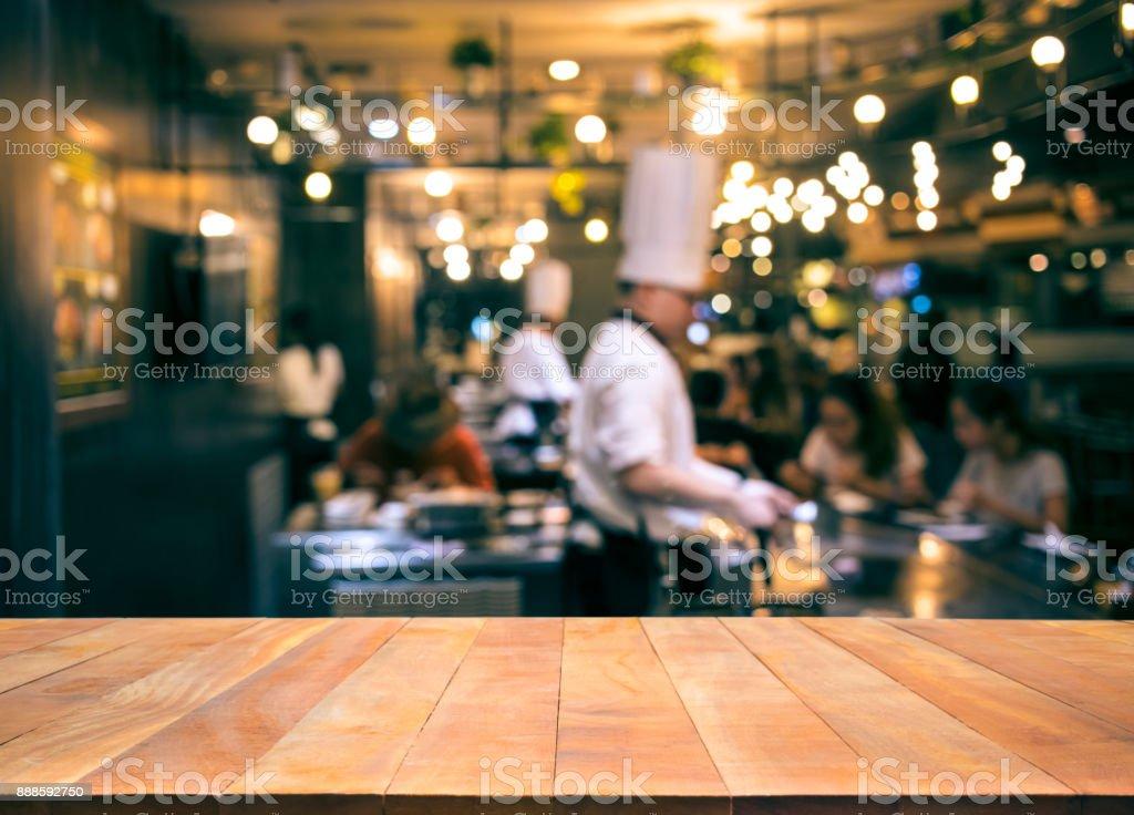 Mesa madera con desenfoque de chef de cocina en bar restaurante - foto de stock