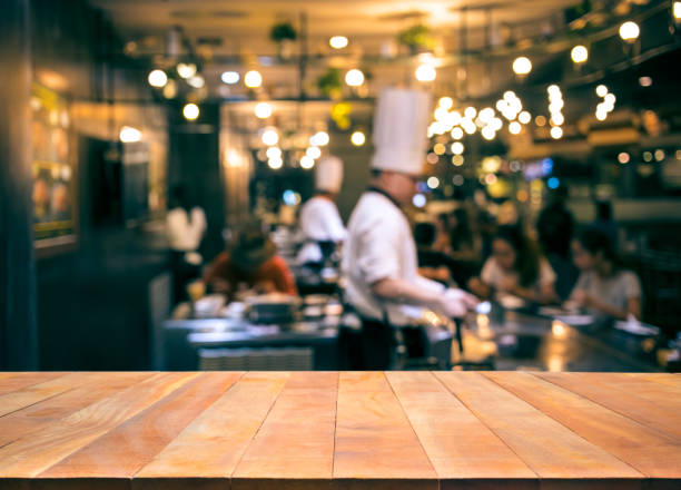wood table top with blur chef cooking in bar restaurant - busy restaurant kitchen stock pictures, royalty-free photos & images