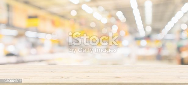 istock Wood table top with blur grocery store background with bokeh light 1050964324