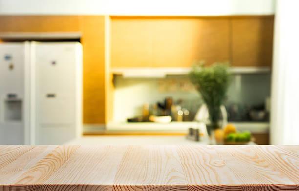 wood table top with blur kitchen room interior  background. - kochinsel stock-fotos und bilder