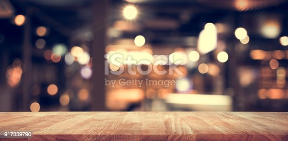 istock Wood table top (Bar) with blur light bokeh in dark night cafe,restaurant background 917339790