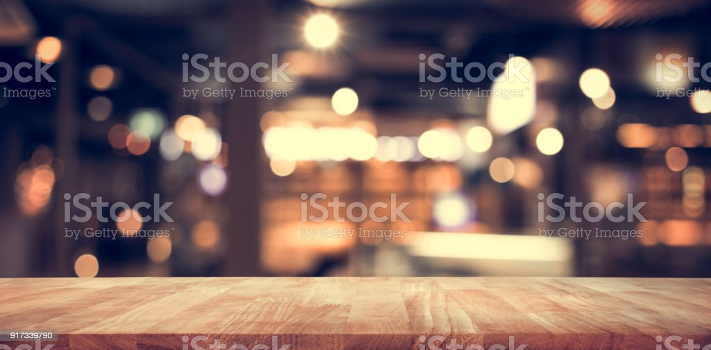 Wood table top (Bar) with blur light bokeh in dark night cafe,restaurant background stock photo