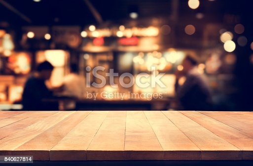 istock Wood table top with blur night cafe background 840627814
