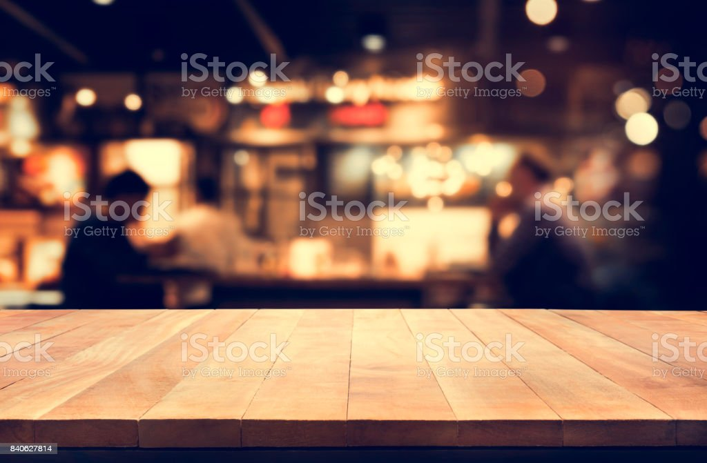 Wood table top with blur night cafe background stock photo