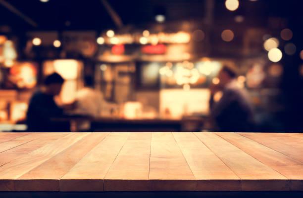 holz-tischplatte mit nacht café hintergrund weichzeichnen - tresentisch stock-fotos und bilder