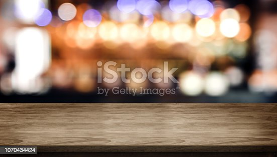 istock Wood table top with blur nightclub bar counter with bokeh light background,banner mock up for display of product or design content. 1070434424