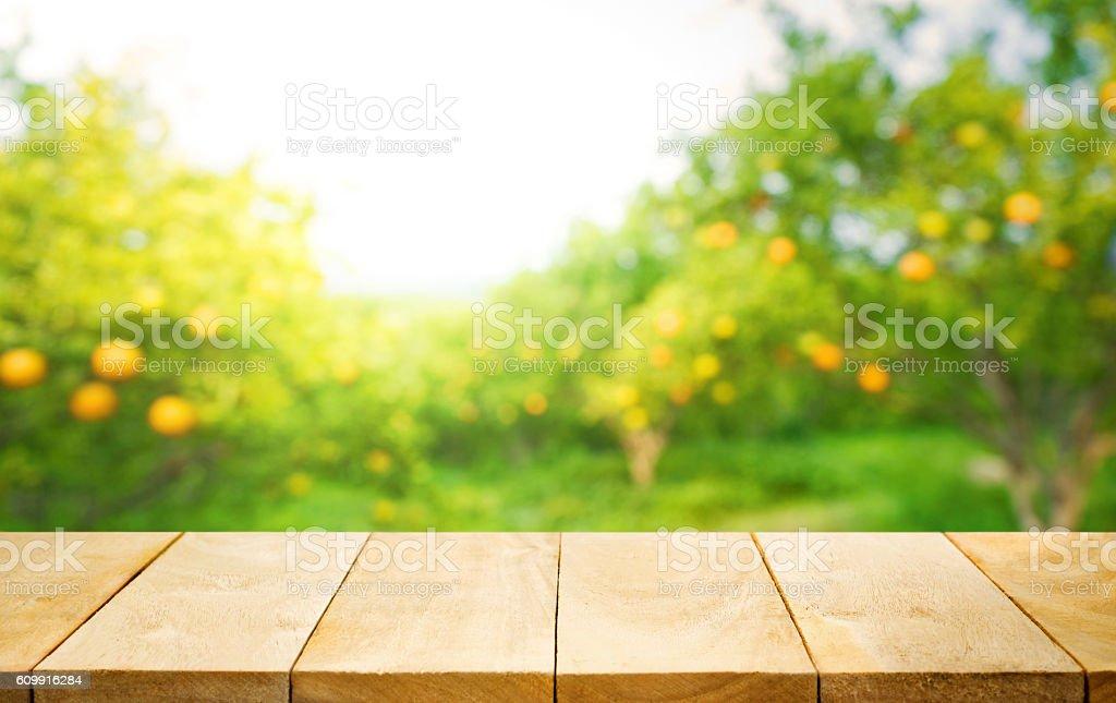 Wood table top with blur of orange garden farm.