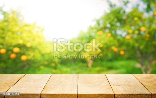 istock Wood table top with blur of orange garden farm. 609916284