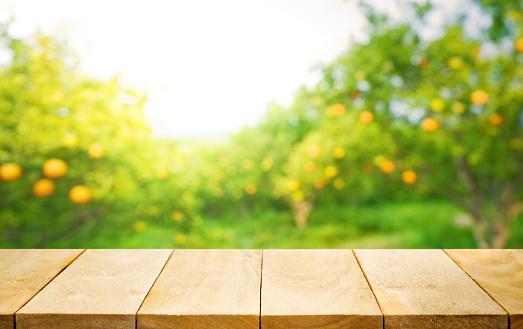 istock Wood table top with blur of orange garden farm. 609916284