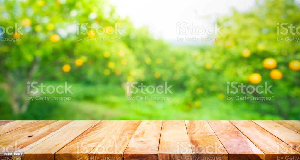 Wood table top with blur of orange garden farm. stock photo