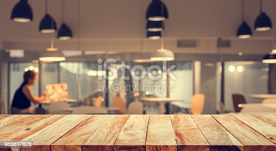 862429776 istock photo Wood table top with blur of people in coffee shop or (cafe,restaurant )background 955517828