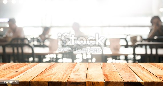 862429776 istock photo Wood table top with blur of people in coffee shop or (cafe,restaurant )background 964948152