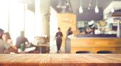 木製テーブルの上のコーヒー ショップやカフェ (レストラン) の人々 の背景のぼかし