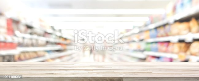 istock Wood table top with blur supermarket in background, panoramic banner 1001168034
