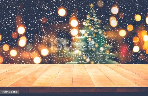 istock Wood table top with snowfall and christmas tree in cafe 852630806