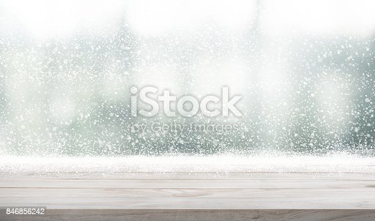 istock Wood table top with snowfall of winter season background. 846856242