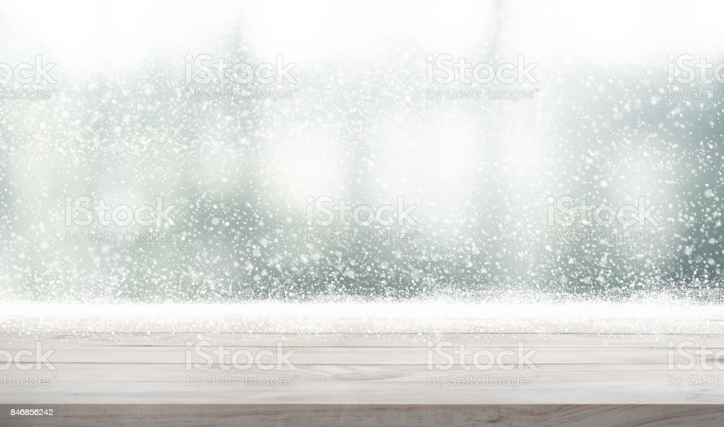 Wood table top with snowfall of winter season background. stock photo