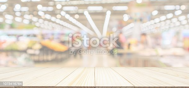 istock Wood table top with supermarket grocery store blurred defocused panorama background with bokeh light for product display 1073416764