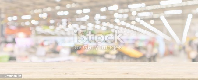 istock Wood table top with supermarket grocery store blurred defocused panorama background with bokeh light for product display 1076945796