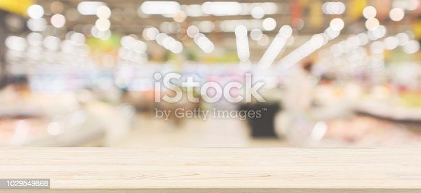 istock Wood table top with supermarket grocery store blurred defocused background with bokeh light 1029549868