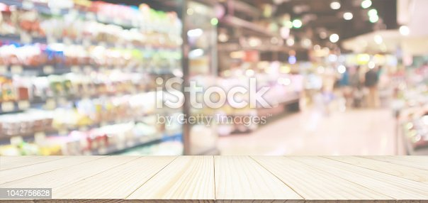 istock Wood table top with supermarket grocery store blurred defocused background with bokeh light 1042756628