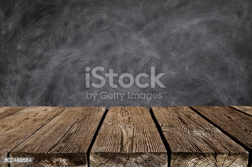 Empty rustic wooden table with black chalkboard at background. Predominant colors are black and brown. Ideal for product display