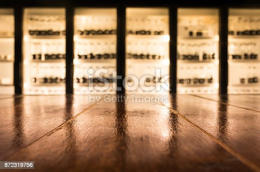862429776 istock photo Wood table with blur counter bar in night cafe/selective focus 872319756