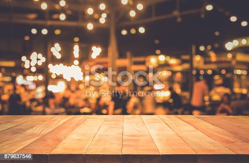 864907996istockphoto Wood table with blur light bokeh in dark night cafe 879637546
