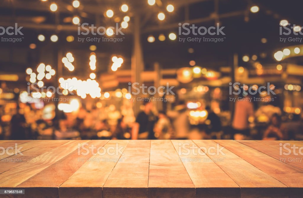Wood table with blur light bokeh in dark night cafe stock photo